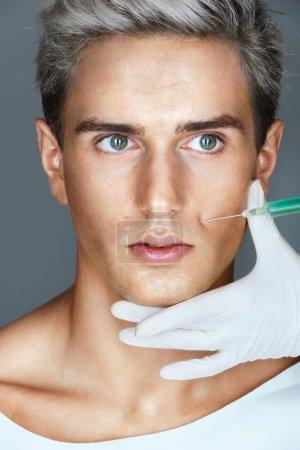 Photo pour Glamour homme reçoit injection de Botox dans les plis naso-labiaux. Portrait d'un homme séduisant lors d'une réception à l'esthéticienne. Concept de beauté - image libre de droit