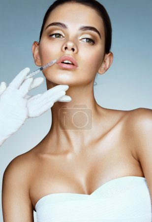 Beautiful woman face and beautician hands with syringe.