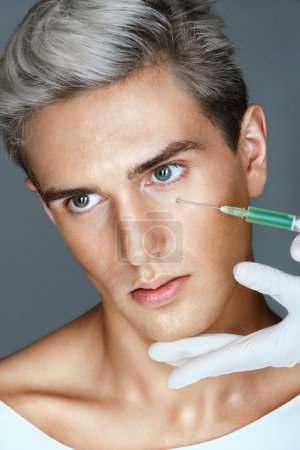 Beautiful young man gets beauty injection in eye area from nurse.