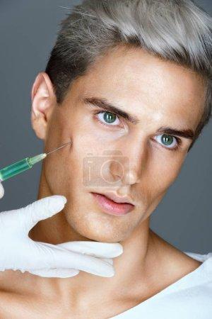 Attractive man getting lifting botox injection in cheekbones.
