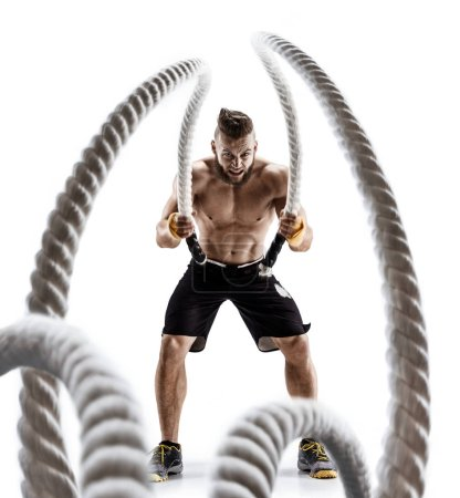 Attractive muscular man working out with heavy ropes