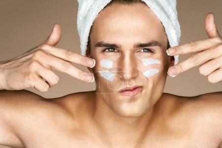 Photo pour Jeune homme avec crème hydratante crème sur le visage. Photo d'homme avec une peau parfaite. Concept de soins de beauté de la peau & - image libre de droit