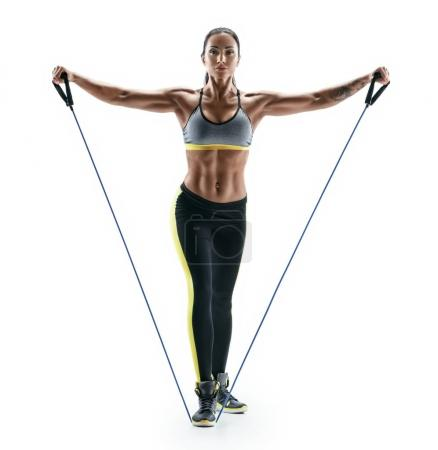 Photo pour Jolie femme musclée effectue des exercices pour les muscles deltoïdes utilisant une bandes de résistance. Photo de jeune brune isolé sur fond blanc. Force et motivation - image libre de droit