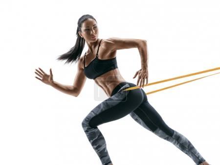 Photo pour Femme forte à l'aide d'une bande de résistance dans sa routine d'exercice. Jeune femme effectue des exercices de fitness sur fond blanc. - image libre de droit