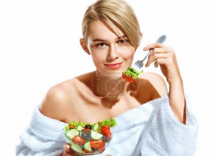 Photo pour Belle femme avec salade de sourire au petit déjeuner le matin. Photo de jeune blonde en peignoir isolé sur fond blanc. Régime alimentaire. Mode de vie sain - image libre de droit