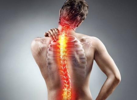 Photo for Young man holding his neck in pain on gray background. Medical concept - Royalty Free Image