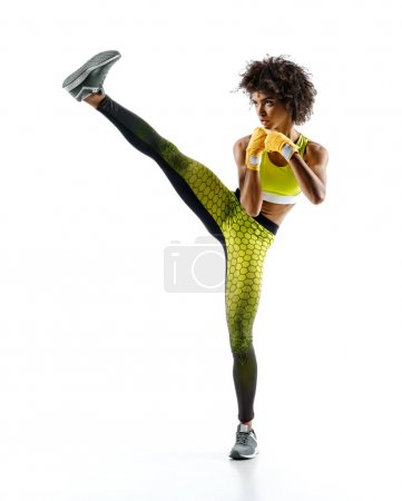 Girl practicing tae-bo exercises, kicking forward with legs. Photo of sporty african girl wearing sports clothes over white background