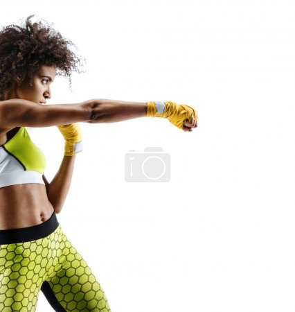 Photo for Boxer woman in yellow bandages making direct hit. Photo of sporty african woman during boxing on white background. Dynamic movement. Side view - Royalty Free Image