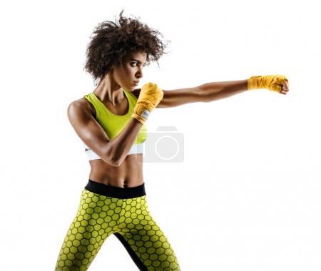 Photo pour Boxer femme faisant directement frappé. Photo de femme africaine sportive au cours de boxe sur fond blanc. Mouvement dynamique. Vue de côté - image libre de droit