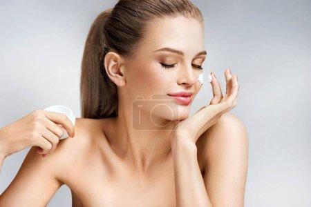 Photo pour Jolie femme, appliquer la crème hydratante sur fond gris. Concept de soins de beauté de la peau & - image libre de droit