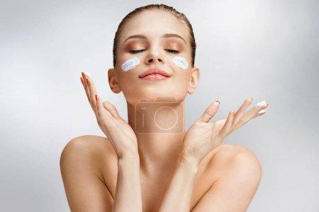 Photo pour Belle femme, appliquer la crème hydratante sur son visage. Photo de femme avec une peau impeccable sur fond gris. Concept de soins et beauté de peau - image libre de droit