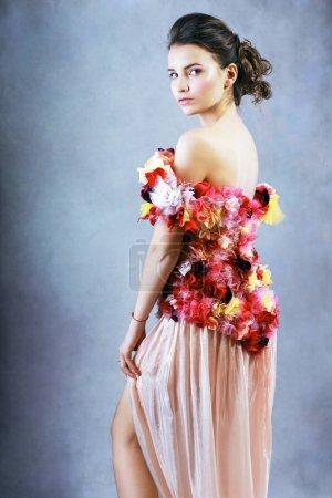 Photo pour Vue de la jeune femme en robe de fleurs en regardant la caméra - image libre de droit