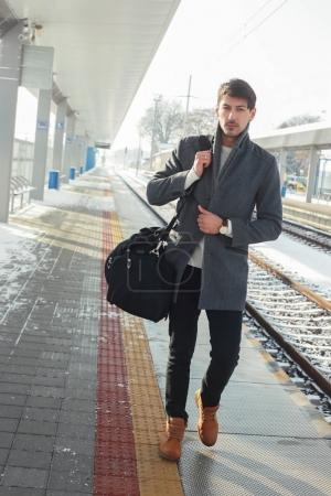 outdoor portrait of young handsome man walking in a hurry at train station wearing warm coat
