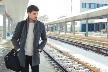 outdoor portrait of young handsome man standing at train station wearing warm coat