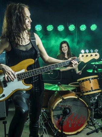 Photo pour Photo d'une femelle bassiste et batteur d'un groupe de rock sur scène. - image libre de droit