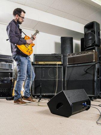 Photo pour Photo d'un homme jouant de sa guitare électrique dans un studio d'enregistrement devant amplificateurs. - image libre de droit