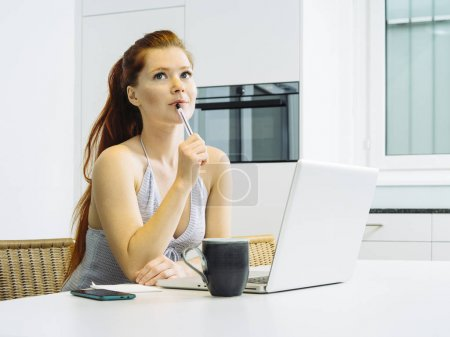 Photo for Photo of a beautiful young woman with red hair sitting with a laptop and thinking. - Royalty Free Image