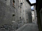 Empty street with stone houses in the historic old village in Bormio, Italy