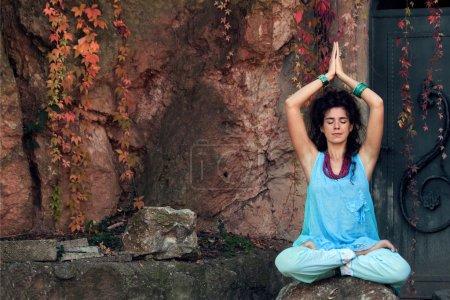 Photo pour Jeune femme pratique le yoga en plein air sur le rocher, position lotus - image libre de droit