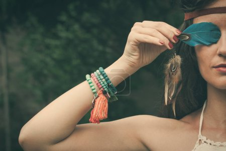 Young bohemian fashion style woman with feather po...
