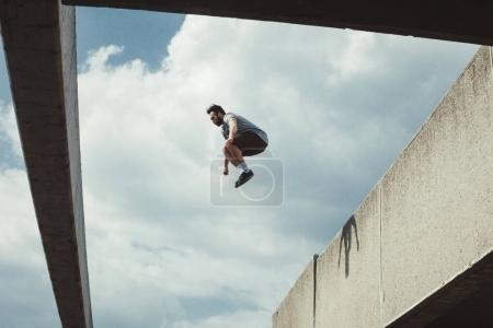 young man doing parkour jump  in the city