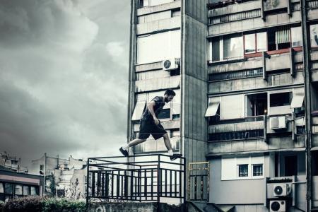 Photo pour Jeune homme faisant du parkour dans l'espace urbain de la ville - image libre de droit