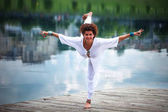woman practice yoga outdoor by the lake