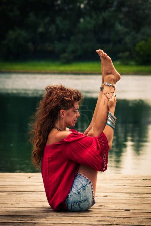 young woman practice yoga  by the lake