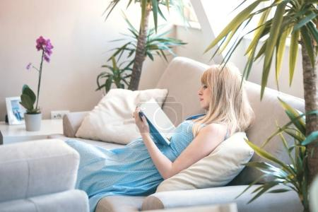pregnant woman reading book in apartment
