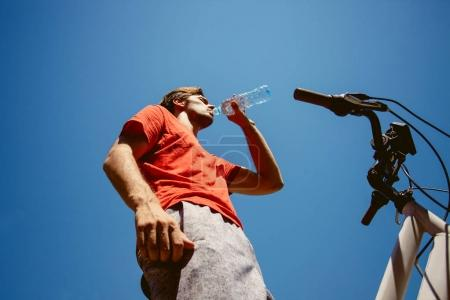 young man on a bicycle drink water from below shot