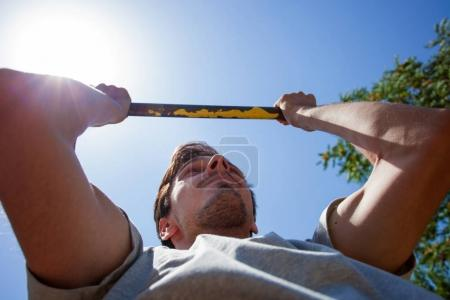 young man doing pull ups outdoor summer day close up