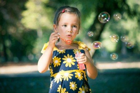 cute little girl play in park blow soap bubbles