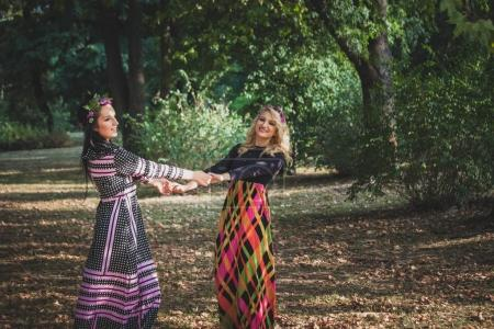 couple of boho style women play or  dance in  park summer day