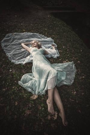 barefoot bride lie on gras and leaves with veil around her