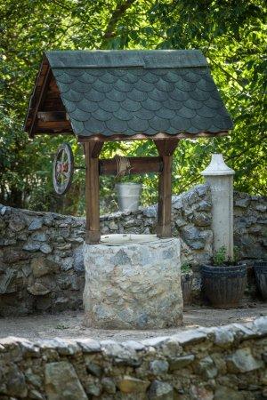 Photo pour Puits de pierre avec seau d'eau en métal dans le village de montagne traditionnel - image libre de droit