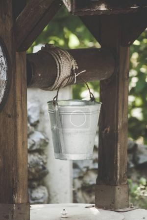 Photo pour Seau d'eau en métal sur puits en bois dans le village traditionnel gros plan - image libre de droit