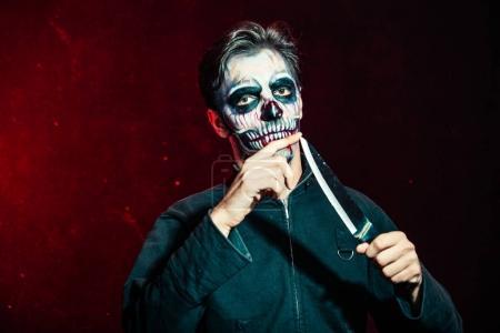 scary halloween skeleton man in jacket hold big knife studio sho