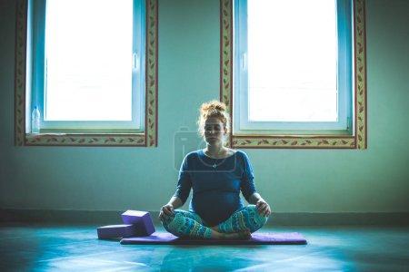 Photo pour Tête rouge jeune femme enceinte en cours de yoga méditation intérieure - image libre de droit