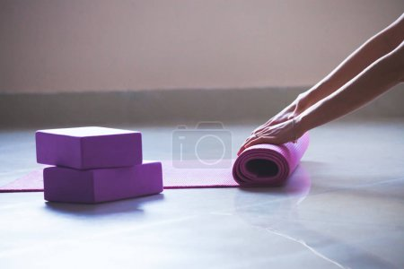 woman rolling yoga mat indoor shot natural  light