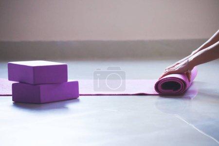 woman rolling yoga mat indoor shot natural  light