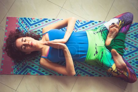 woman lie on yoga  mat with hands in namaste gesture and legs in