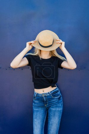 Photo for Young blonde woman in casual black t shirt and hat against blue metal background outdoor in city t shirt mock up - Royalty Free Image