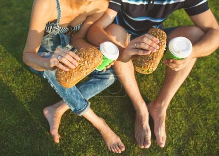 couple sitting on the grass in the park and eating sandwiches sm
