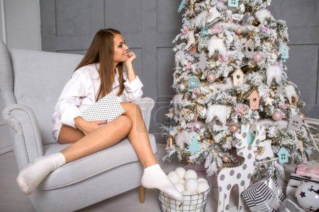 girl at Christmas dreams near the Christmas tree with gifts, the
