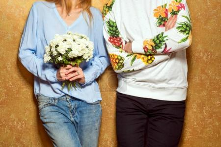 hipster couple in love with a bouquet of flowers in the studio,