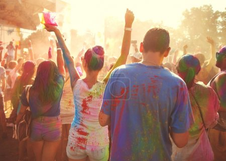 a crowd of people celebrating the Holi festival at sunset