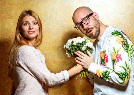 Photo pour Couple de mode émotionnelle se donnent des fleurs le jour de la Saint-Valentin. Style Vogue - image libre de droit