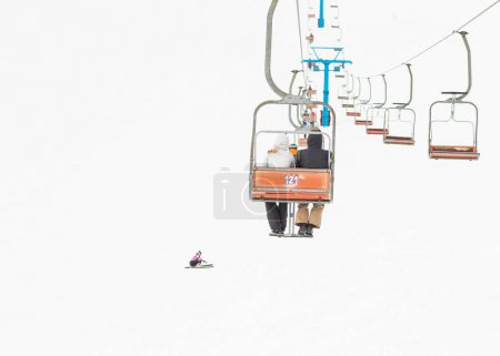 two skiers on a platform on a background of high snow mountains