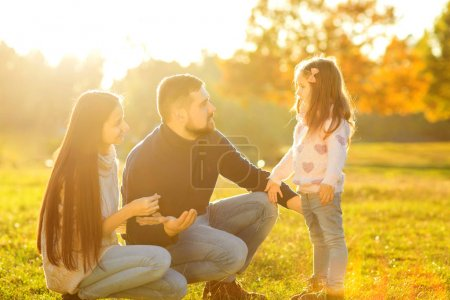 mom and dad with daughter at sunset playing