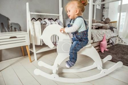 one year old girl playing near in the room with a toy horse, ska